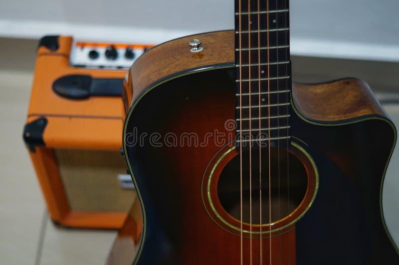 Akustisk gitarr och högtalare med bokeh royaltyfri foto