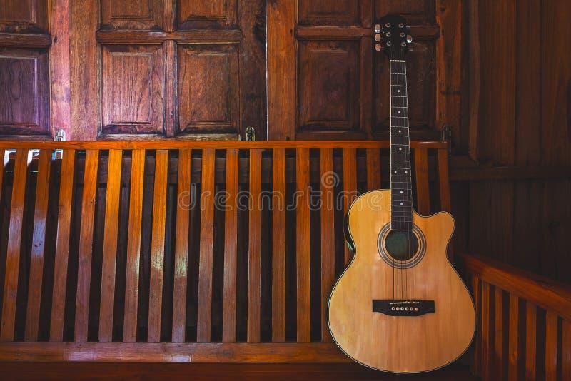 Akustisk gitarr som förläggas på trägolv arkivfoto