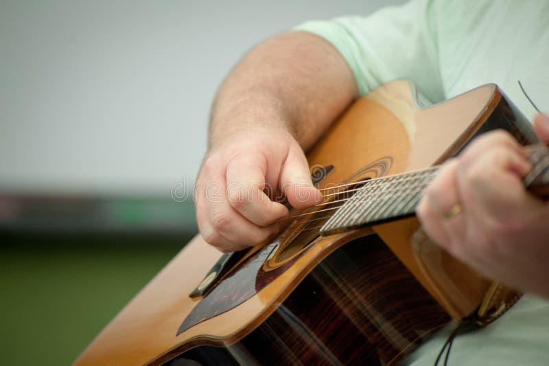 Akustisk gitarr som spelas av en man royaltyfri fotografi