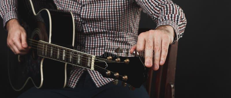 Akustisk gitarr som tätt trimmar och spelar upp royaltyfri bild