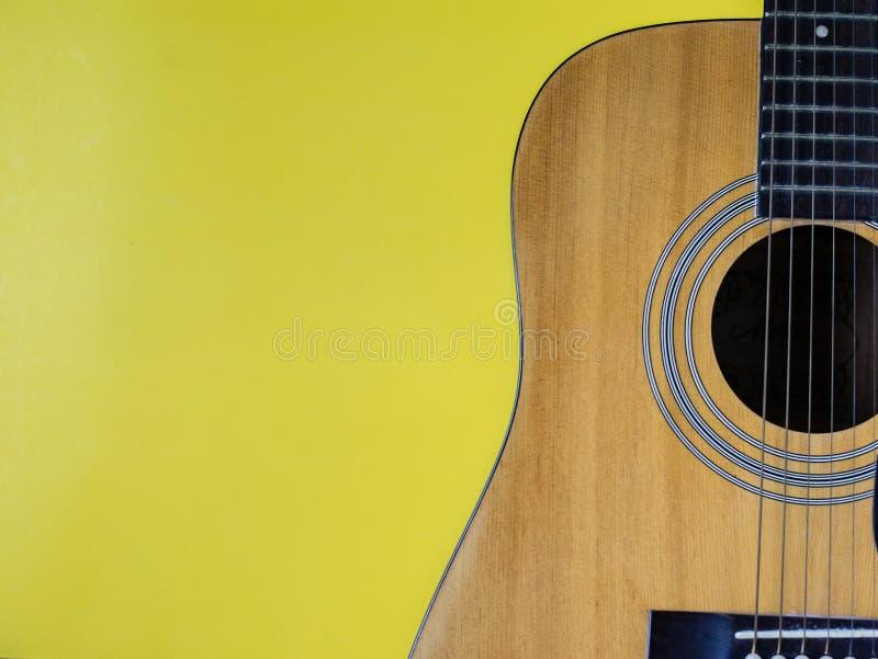 Akustisk gitarr som vilar mot en gul bakgrund med kopieringsutrymme royaltyfri bild