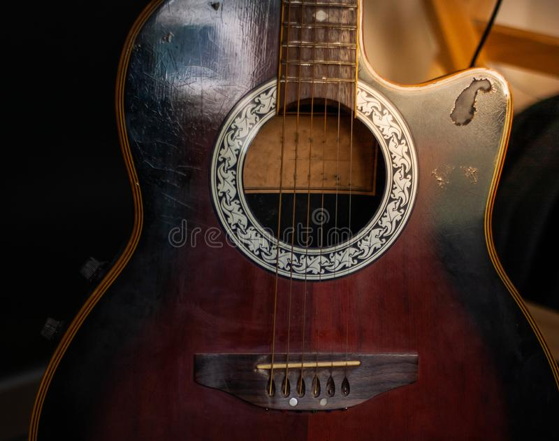 Akustisk gitarr som vilar mot en tr?bakgrund arkivfoto