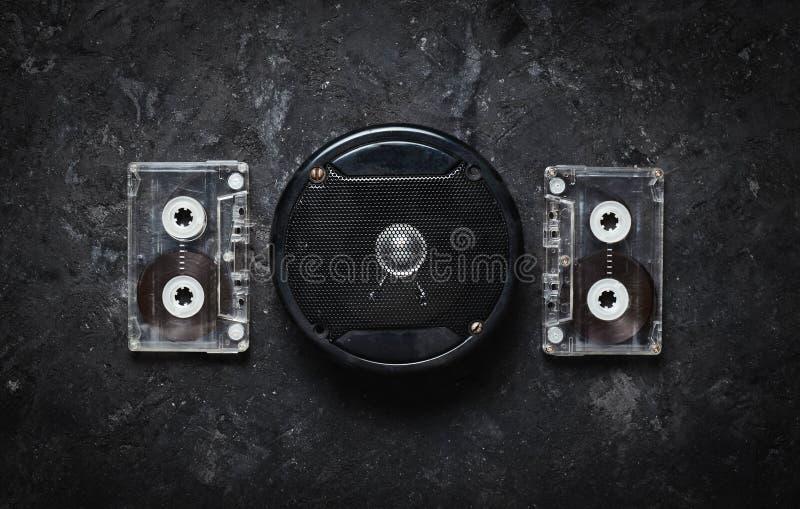 Akustyczny mówca i audio kaseta na czarnym betonu stole Retro technologia Meloman Odgórny widok Mieszkanie nieatutowy fotografia stock