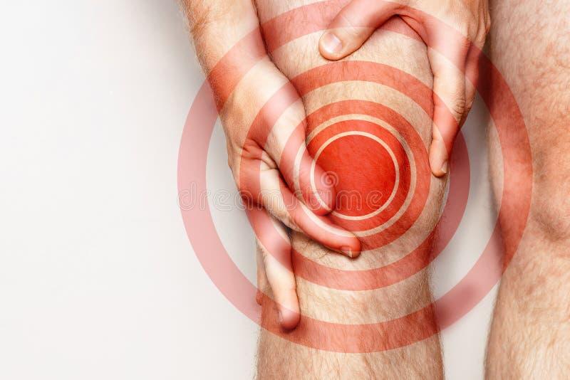 Akut smärta i en knäled, närbild Färgbild, på en vit bakgrund Smärta område av röd färg arkivbilder