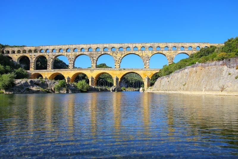 Akvedukten Pont du Gard reflekterade i den Gardon floden, sydliga Frankrike arkivbild