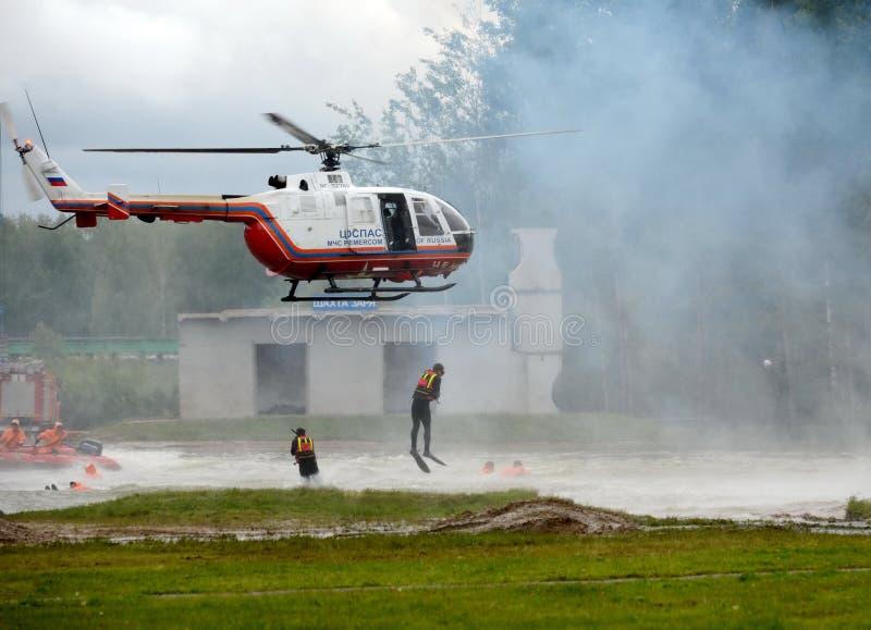 Akwalungów nurkowie opuszczają od BO-105 ` Tsentrospasa śmigłowcowego ` EMERCOM Rosja na pasmie Noginsk ratunek c fotografia stock