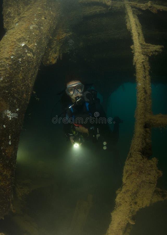 Akwalungu młody żeński Nurek bada shipwreck zdjęcie royalty free