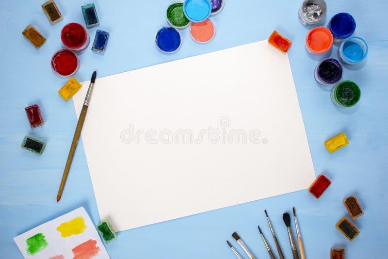 Akwarela, muśnięcia i prześcieradło papier na błękitnym tle, akrylowy, Mieszkanie nieatutowy, odg?rny widok artysty stół zdjęcie stock