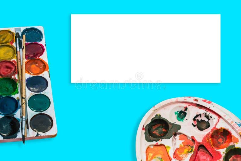Akwareli farby i paleta z punktami na błękitnym tle Farby muśnięcie w farbie Pojęcie rysunek, sztuka zdjęcie stock