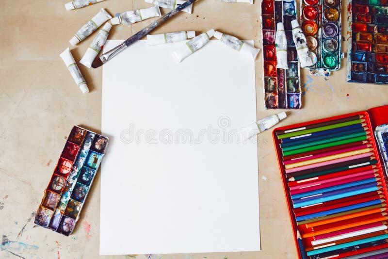 Akwareli farby, pusta biała księga i coloured ołówki na stole w sztuki studiu, obraz stock