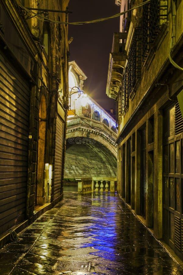 Aléia escura em Veneza com ponte de Rialto fotografia de stock