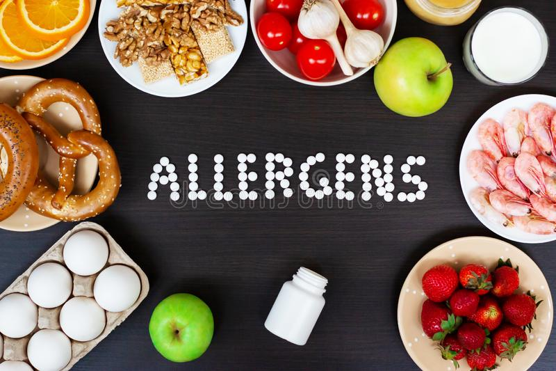 Alérgenos como o leite, laranjas do alimento, tomates, alho, camarão, amendoins, ovos, maçãs, pão, morangos na tabela de madeira foto de stock royalty free