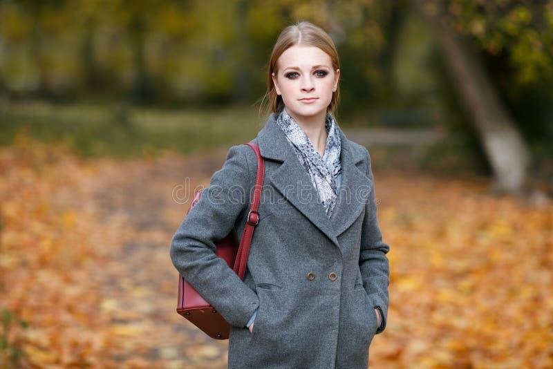 Al aire libre el retrato de la mujer hermosa del pelirrojo con magnífico compone la mochila de cuero roja que da un paseo en Fore fotos de archivo