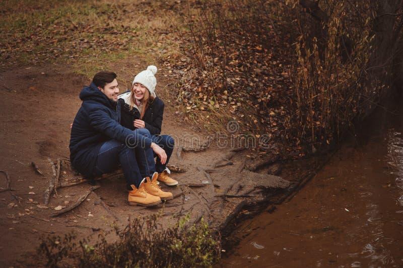 Al aire libre felices de los pares jovenes cariñosos juntos en acogedor calientan el paseo en bosque del otoño imagen de archivo
