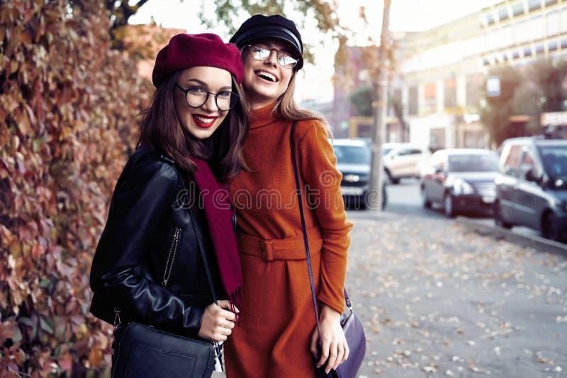 Al aire libre forme a los amigos de muchachas de los jóvenes del retrato bastante mejor en abrazo amistoso El caminar en la ciuda fotos de archivo