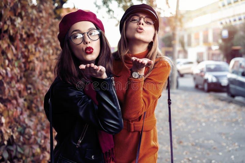 Al aire libre forme a los amigos de muchachas de los jóvenes del retrato bastante mejor en abrazo amistoso El caminar en la ciuda foto de archivo libre de regalías