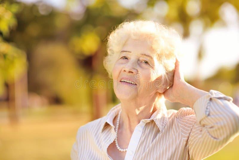 Al aire libre retrato de la mujer mayor sonriente hermosa con el pelo blanco rizado fotografía de archivo libre de regalías