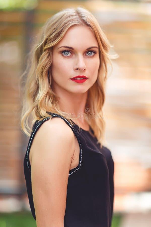 Al aire libre retrato de la mujer rubia atractiva joven que lleva la blusa negra fotos de archivo