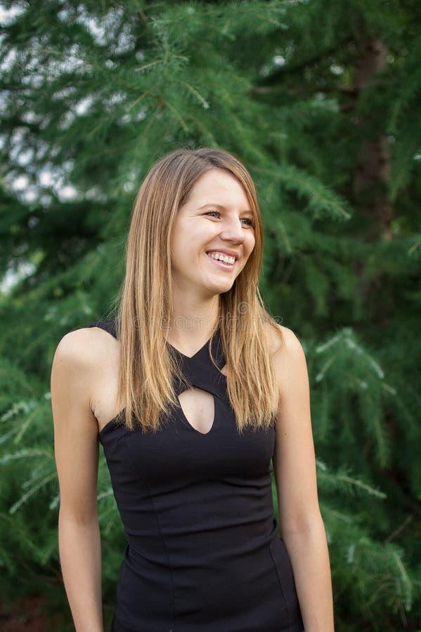 Al aire libre retrato de la mujer sonriente atractiva en camisa negra cerca del árbol Spruce durante tiempo de verano foto de archivo
