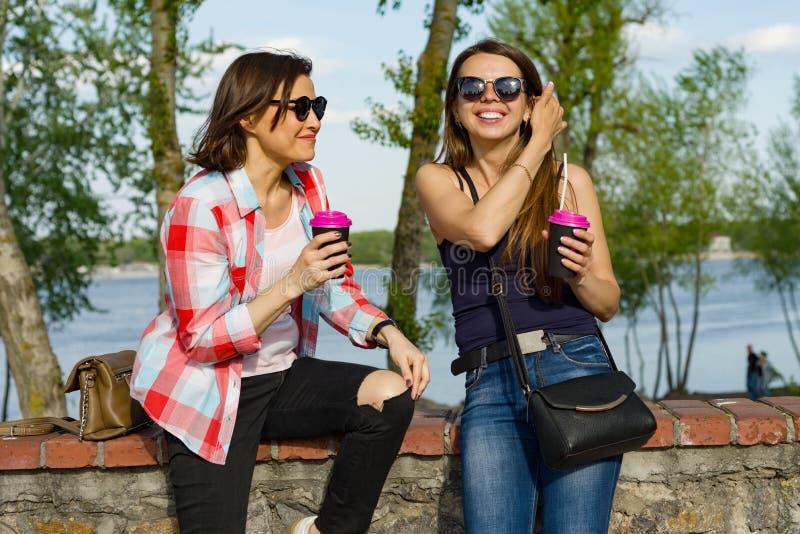 Al aire libre retrato de los amigos femeninos que beben el café y que se divierten Naturaleza del fondo, parque, río Forma de vid imágenes de archivo libres de regalías