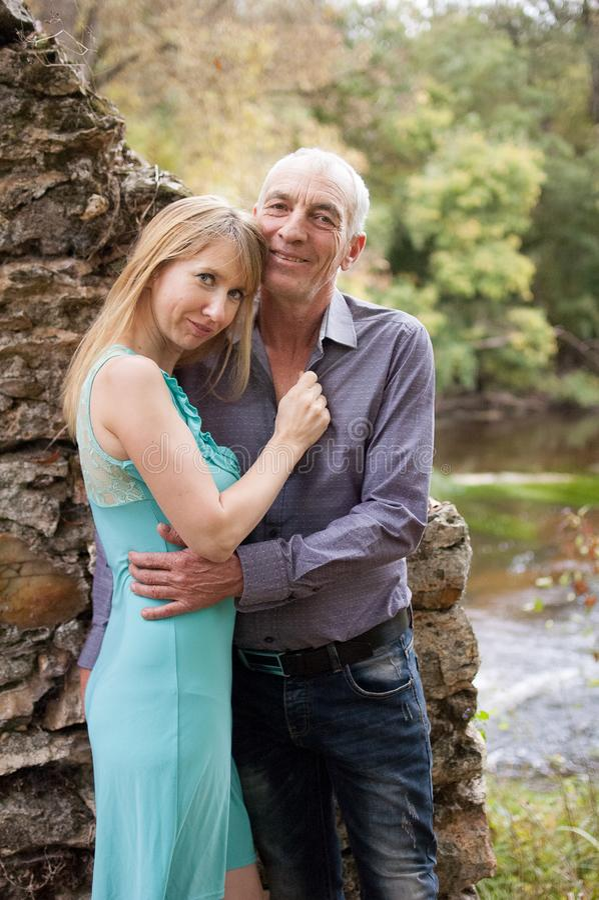 Al aire libre retrato de pares felices con el abrazo de la diferencia de la edad que se coloca en el parque durante Sunny Warm Su imagen de archivo