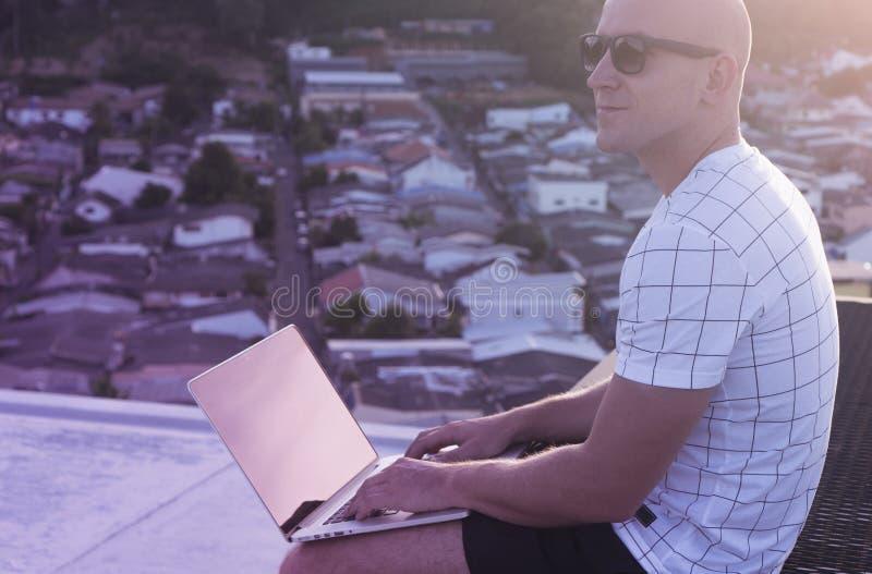 Al aire libre retrato del hombre joven hermoso con el ordenador portátil imagen de archivo libre de regalías