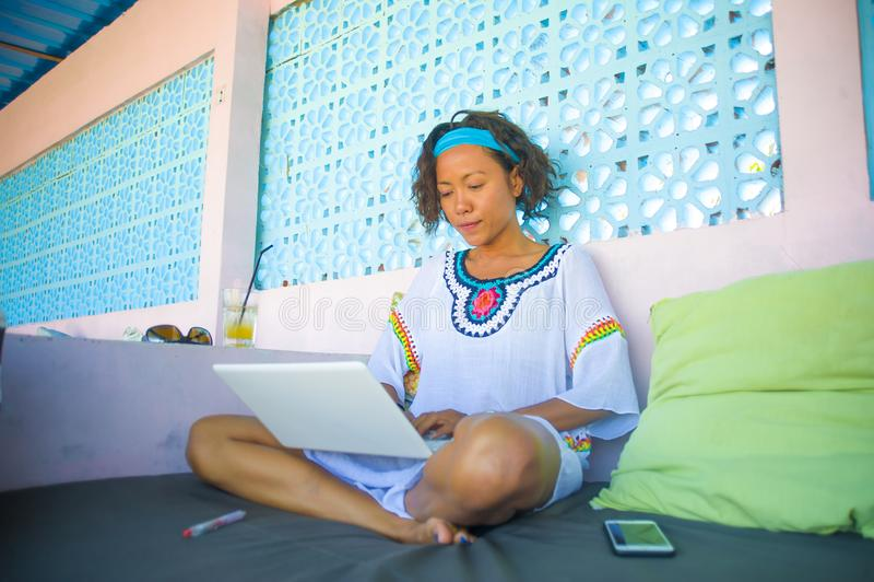 Al aire libre retrato del inconformista atractivo y feliz joven que mira a la mujer que trabaja en línea con el ordenador portáti foto de archivo