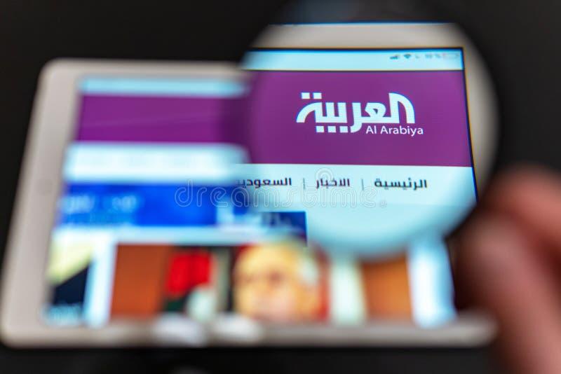 Al Arabiya News kanallogo som är synlig till och med ett förstoringsglas fotografering för bildbyråer