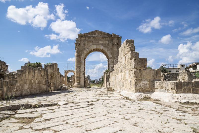 Al-Bass, Byzantine road with triumph arch in ruins of Tyre, Lebanon. Al-Bass, Byzantine road with triumph arch with blue sky and clouds in ruins of Tyre, Lebanon stock photos