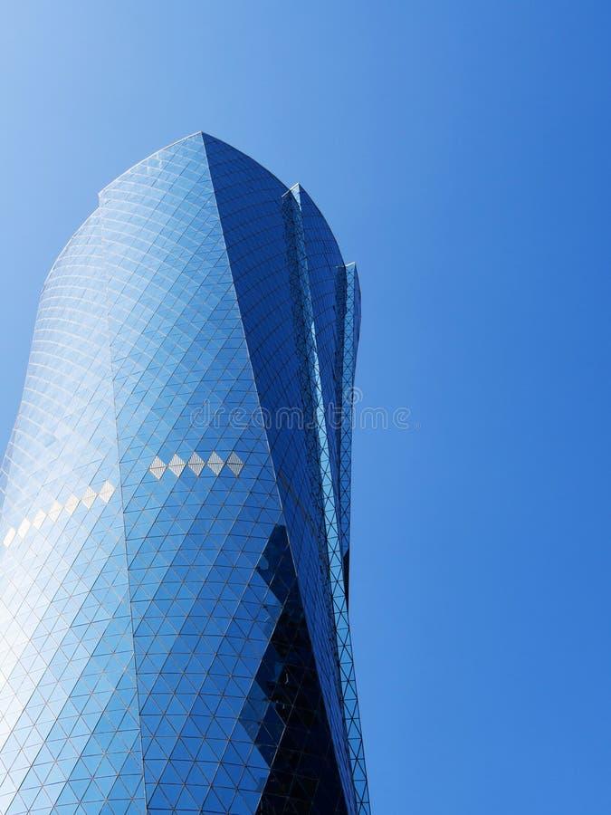 Al Bidda Tower against clear blue sky, close up, copy space, vertical. Financial concept stock photos