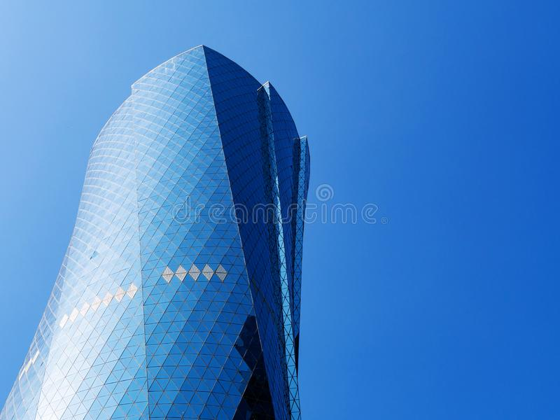 Al Bidda Tower against clear blue sky, close up. Modern skyscraper with glazed facade royalty free stock image