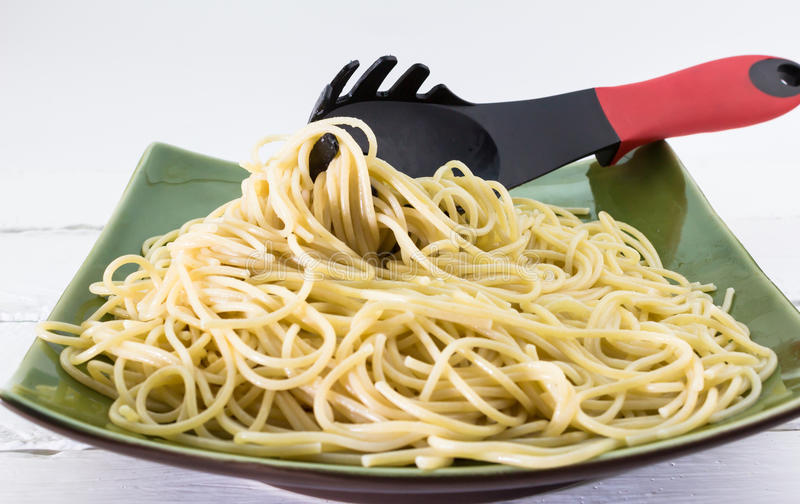 Al dente spaghetti pasta on a plate with pasta fork on white background royalty free stock image