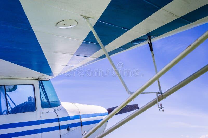 Al di sotto dell'ala piccoli degli aerei d'annata a strisce blu e bianchi con cielo blu soleggiato fotografia stock