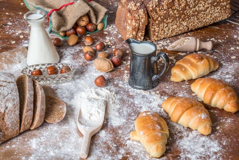 Al forno, alla natura morta con i mini croissant, al pane, al latte, ai dadi ed alla farina immagini stock