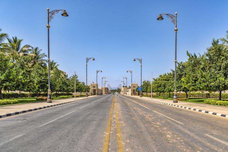 AL Fujayrah Förenade Arabemiraten Sikten av en tom stenlagd gata, med härliga förgyllda streetlights markerade fot- gångbanor, p royaltyfria bilder
