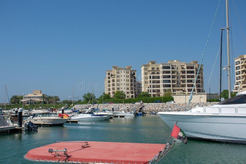 Al Hamra, Ras al Khaimah, porto de Emiratos Árabes Unidos com barcos e apartamentos e água azul e céu imagens de stock