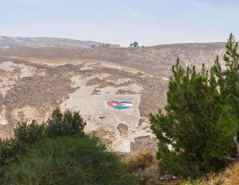 View from the walls of the fortress on the Jordanian flag painted in the shape of a heart on the surface of a nearby hill near Al stock image
