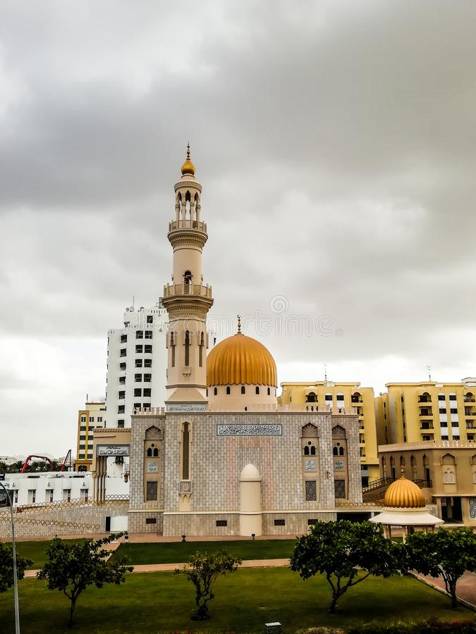 Al Khuwair Zawawi Mosque right view in front of Muscat main road. In cloudy weather having beautiful sky with greenery Muscat Oman raining in Muscat royalty free stock photo