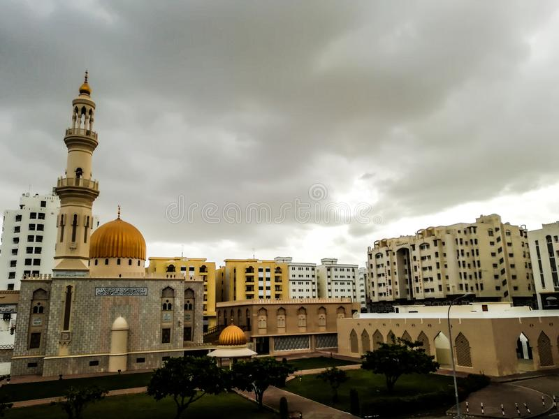 Al Khuwair Zawawi Mosque right view in front of Muscat main road. In cloudy weather having beautiful sky with greenery Muscat Oman raining in Muscat royalty free stock photography