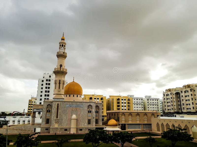 Al Khuwair Zawawi Mosque right view in front of Muscat main road. In cloudy weather having beautiful sky with greenery Muscat Oman raining in Muscat royalty free stock photos