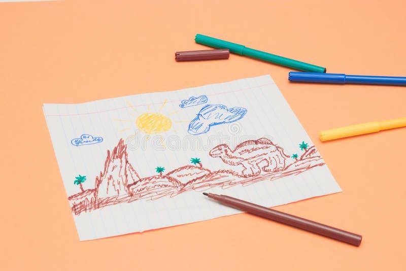 Al lado de los marcadores coloreados es un dibujo de los niños primitivos con un rotulador en un fondo del melocotón Desarrollo i fotos de archivo