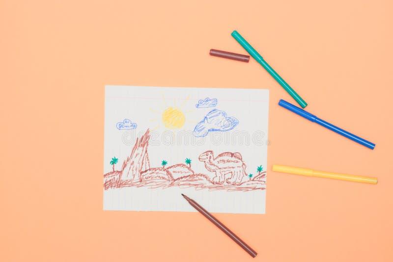 Al lado de los marcadores coloreados es un dibujo de los niños primitivos con un rotulador en un fondo del melocotón Desarrollo i foto de archivo libre de regalías