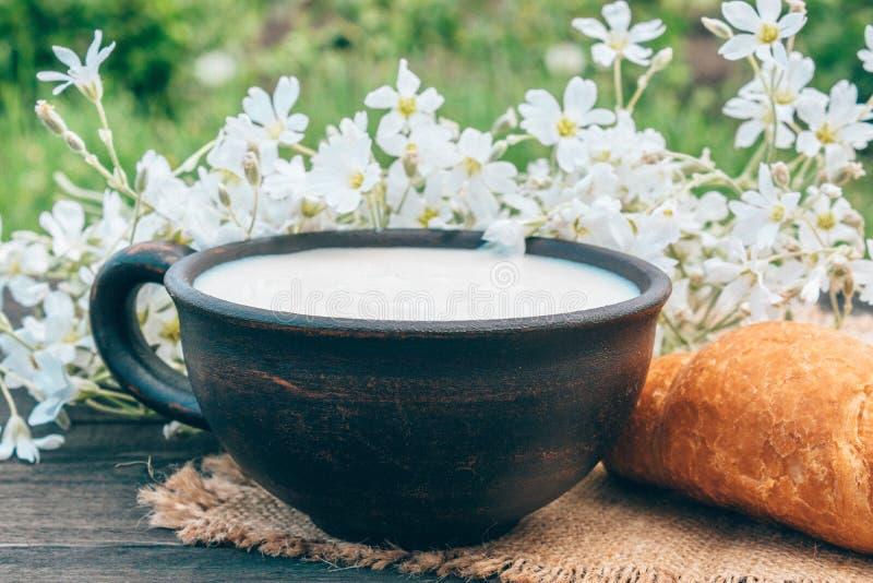 Al lado del cruasán y de las flores blancas es una taza de leche en una servilleta foto de archivo libre de regalías