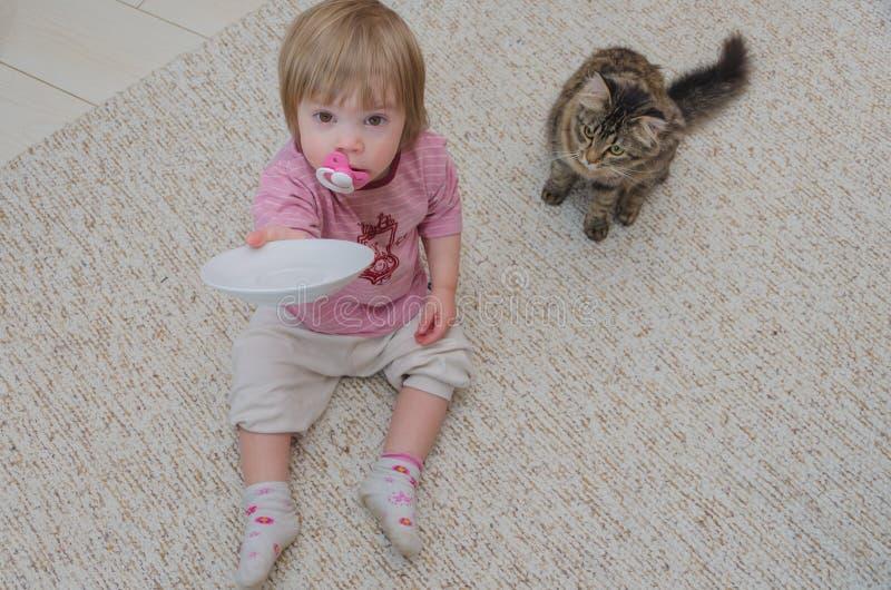Al lado del gato en el piso sienta a un niño, la muchacha quiere a la tarifa imagen de archivo libre de regalías