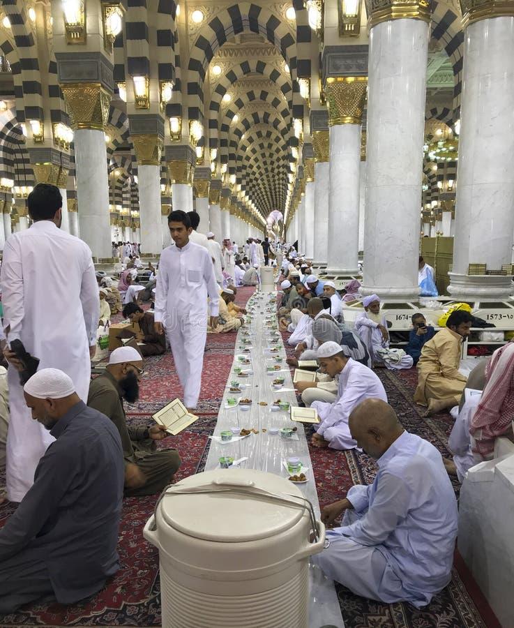 AL MADINAH, SAUDITA ARABIA-CIRCA MAIO DE 2019: Os homens muçulmanos não identificados preparam-se para quebrar rapidamente no alv foto de stock