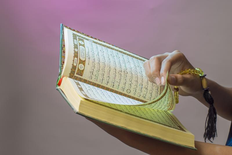 Al-Qur& x27;an. Open Qur& x27;an sheet by the hand holding the prayer beads & x28;tasbih. & x29;. The Qur& x27;an is the holy book of Islam koran arabic islamic stock image