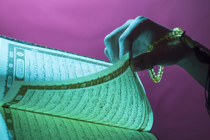 Al-Quran. Open Quran sheet by the hand holding the prayer beads, tasbih. Al-Quran. Open Quran sheet by the hand holding the prayer beads. The Quran is the holy royalty free stock images