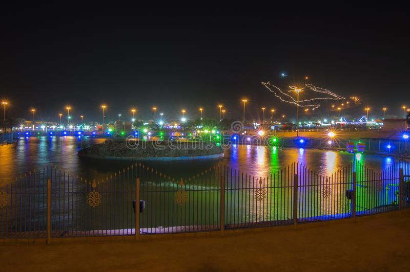 Al Samrah Park in Ha`il, Saudi Arabia. In night time. Colorful bright lights reflect on a small lake. KSA map is lighted on a mountain. Black sky is on the stock photography