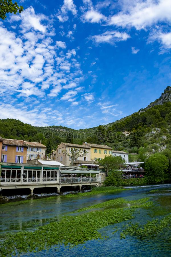 Al sur de Francia, opinión sobre la pequeña ciudad de Provencal del poeta Petrarch Fontaine-de-Vaucluse con aguas verdes esmerald fotografía de archivo