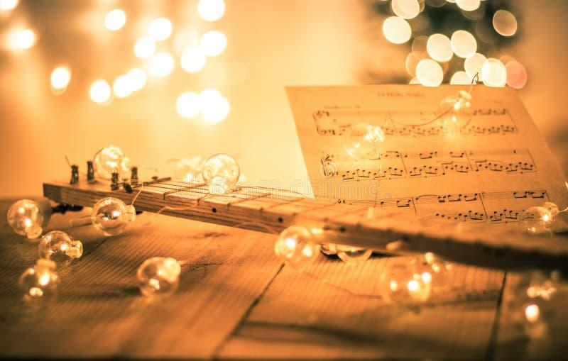 Alaúde com partitura instrumental e luzes suaves para o feriado do Natal, tom da separação imagens de stock